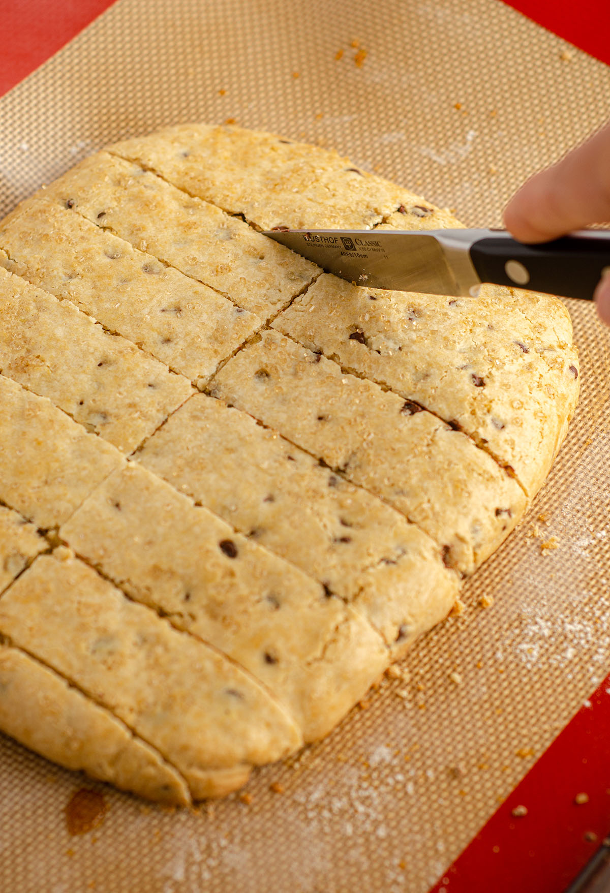 hand cutting biscotti slab into pieces to bake into individual biscotti