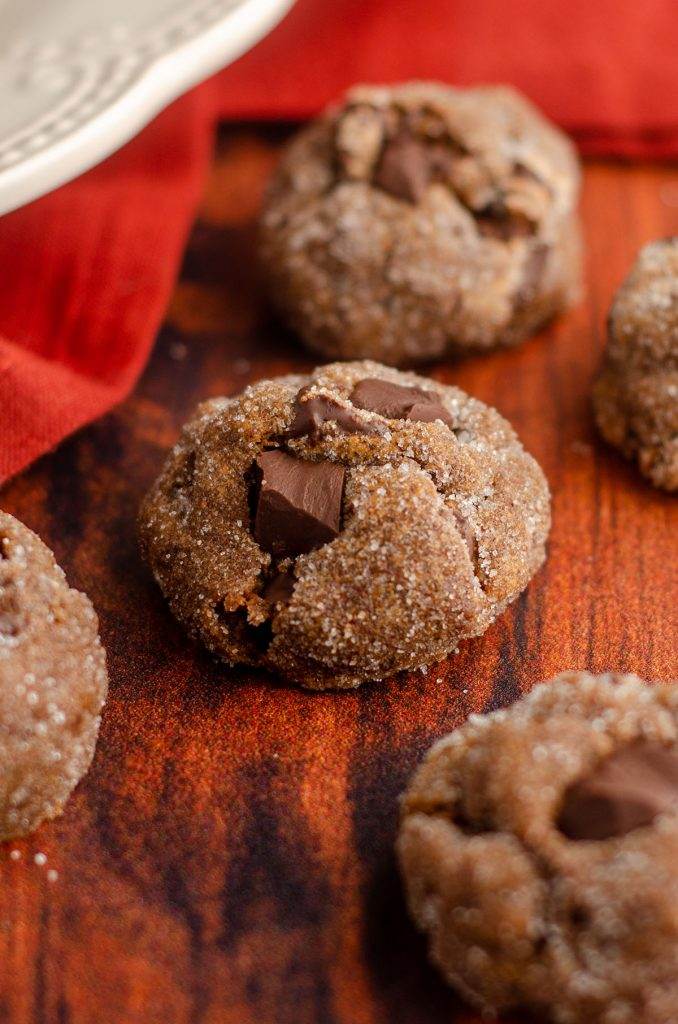 gingerbread chocolate cookie sitting on a wooden surface with burnt red kitchen towel behind it