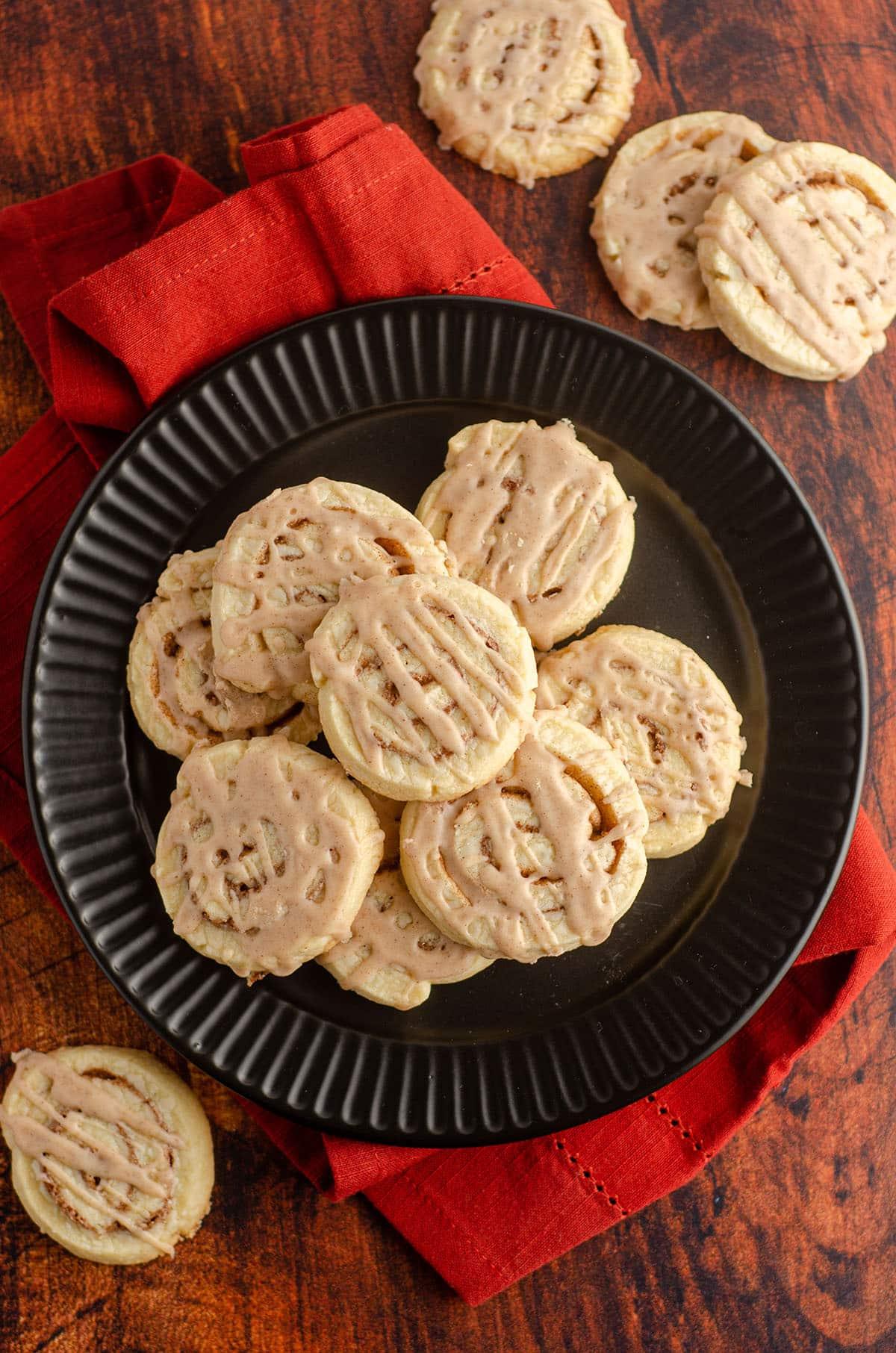 aerial photo of cinnamon pinwheel cookies sitting on a black plate