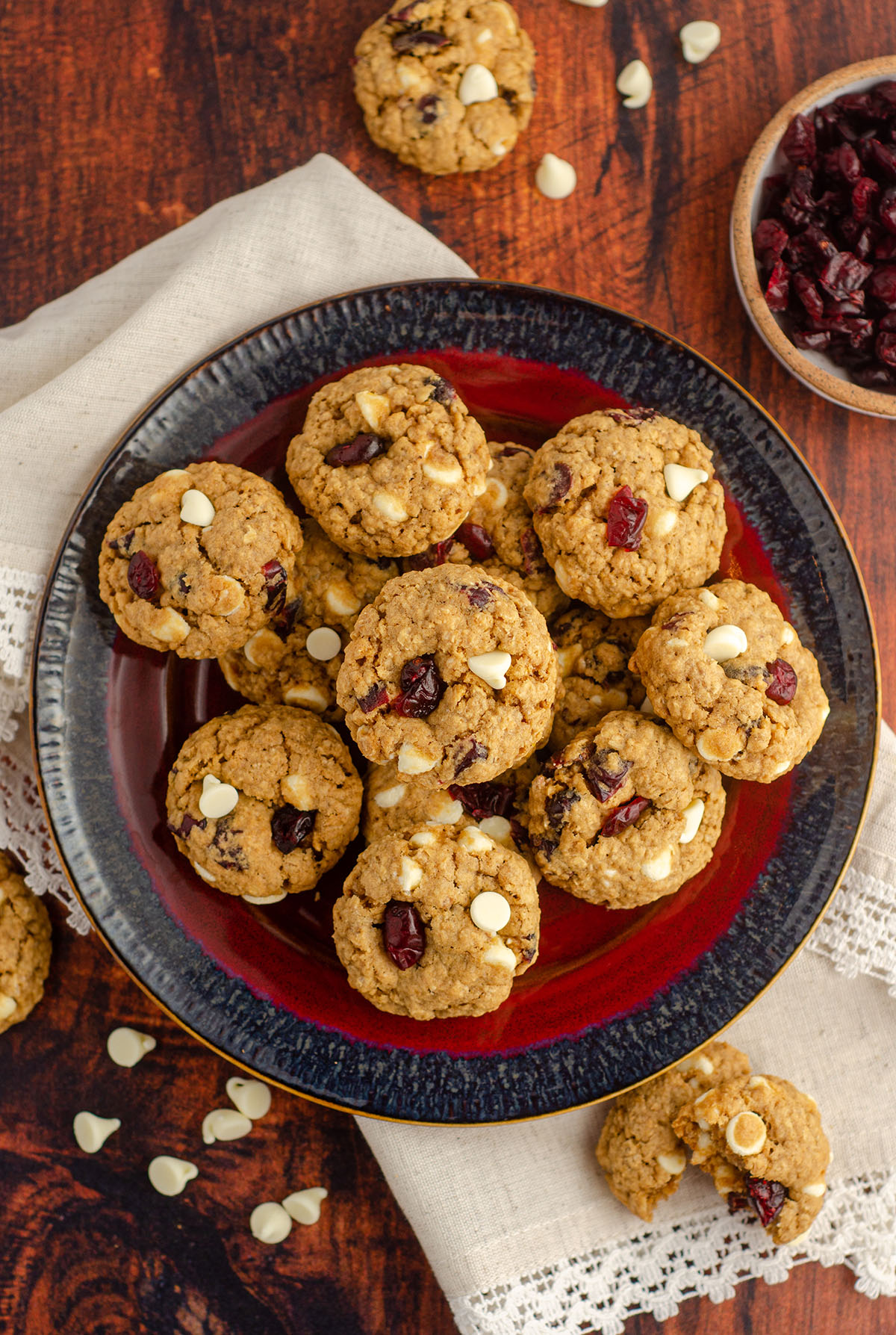 aerial photo of white chocolate cranberry oatmeal cookies sitting on a red and black plate