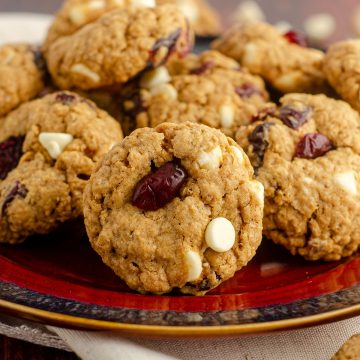 white chocolate cranberry oatmeal cookies sitting on a red and black plate