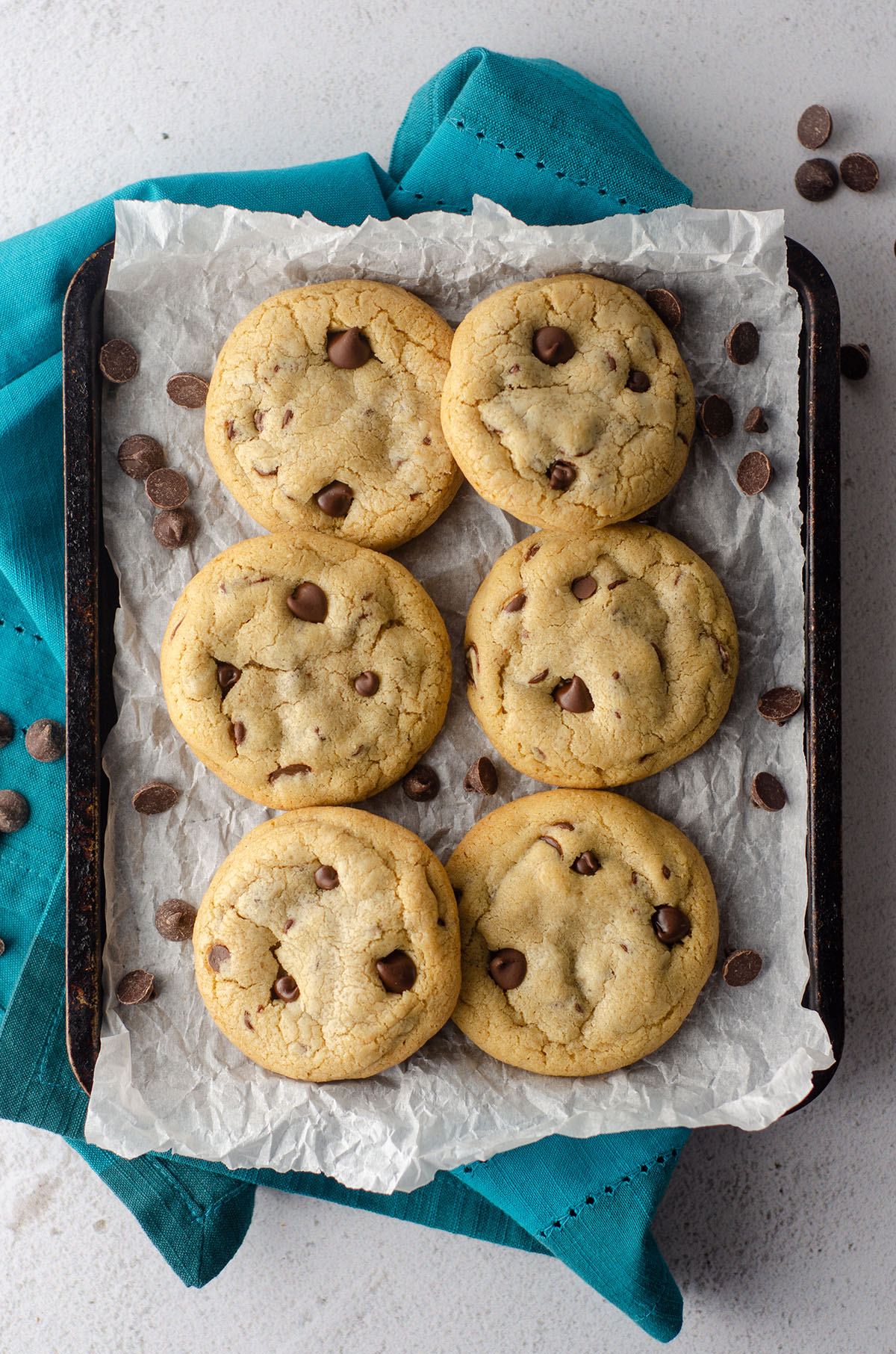 aerial photo of 6 small batch chocolate chip cookies sitting on parchment paper on a baking sheet