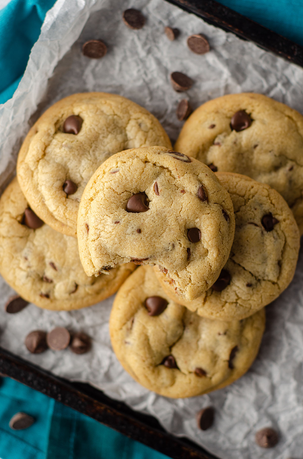 aerial photo of 6 small batch chocolate chip cookies sitting on parchment paper on a baking sheet and a bite is taken out of the one on the top