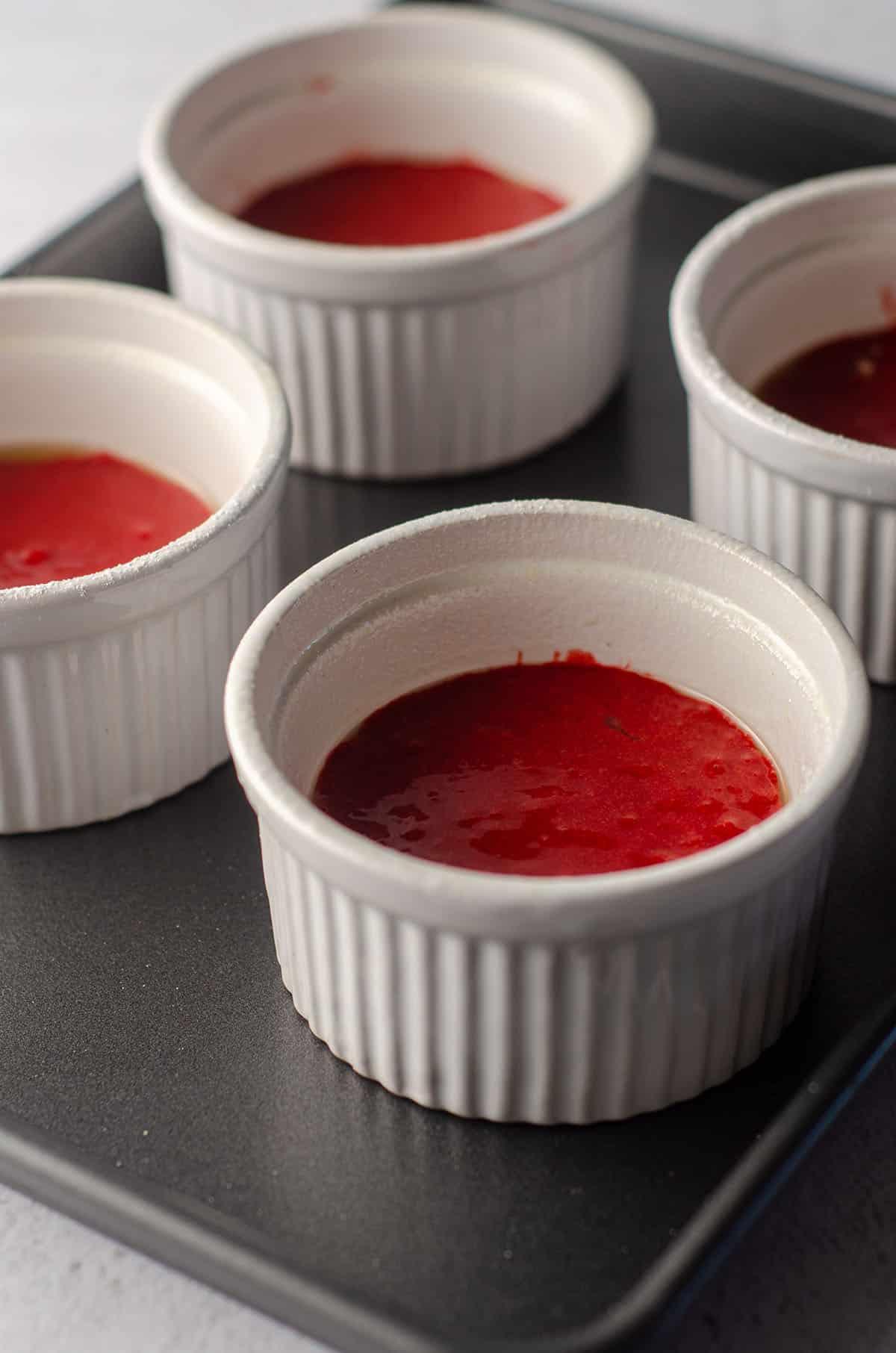 red velvet lava cake batter sitting in ramekins ready to bake
