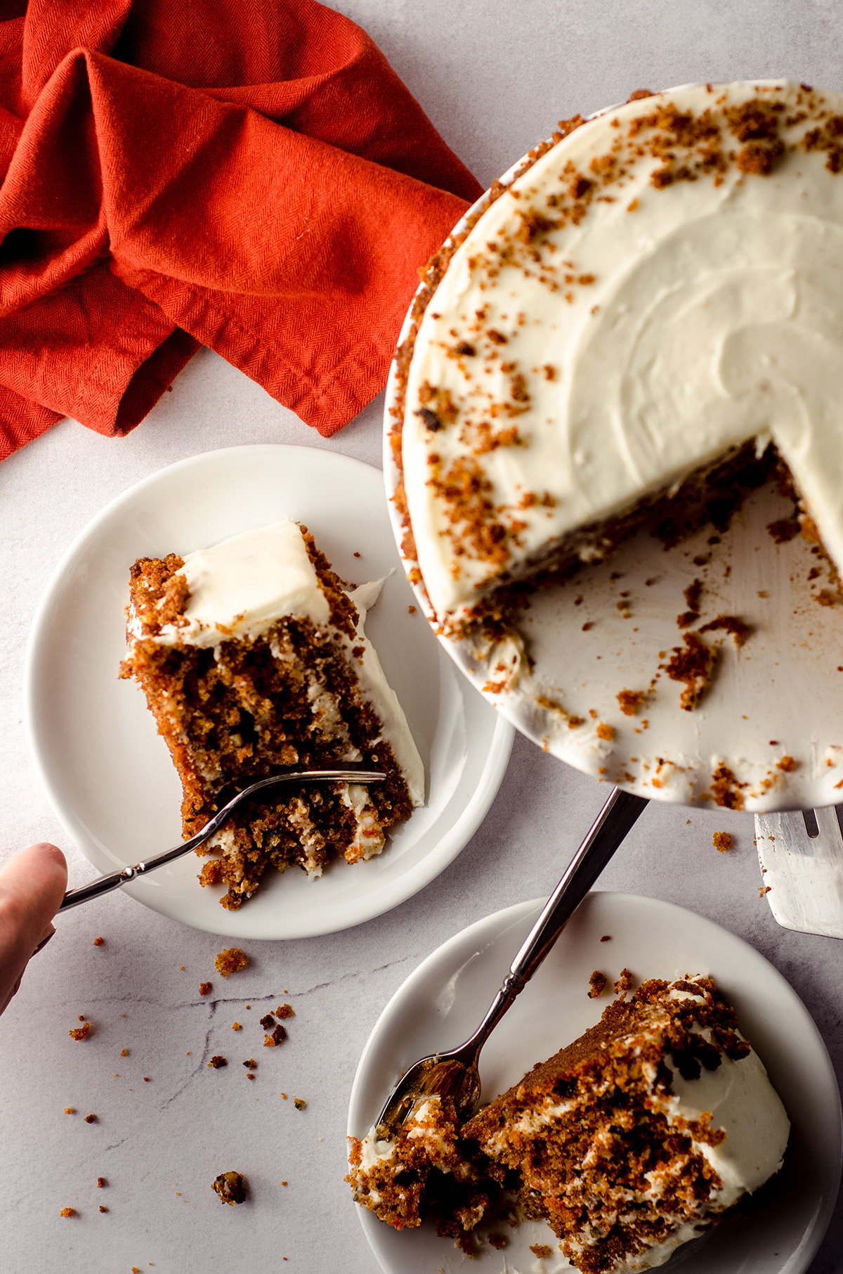 aerial photo of two slices of carrot walnut cake on plates and one has a fork digging into it for a bite