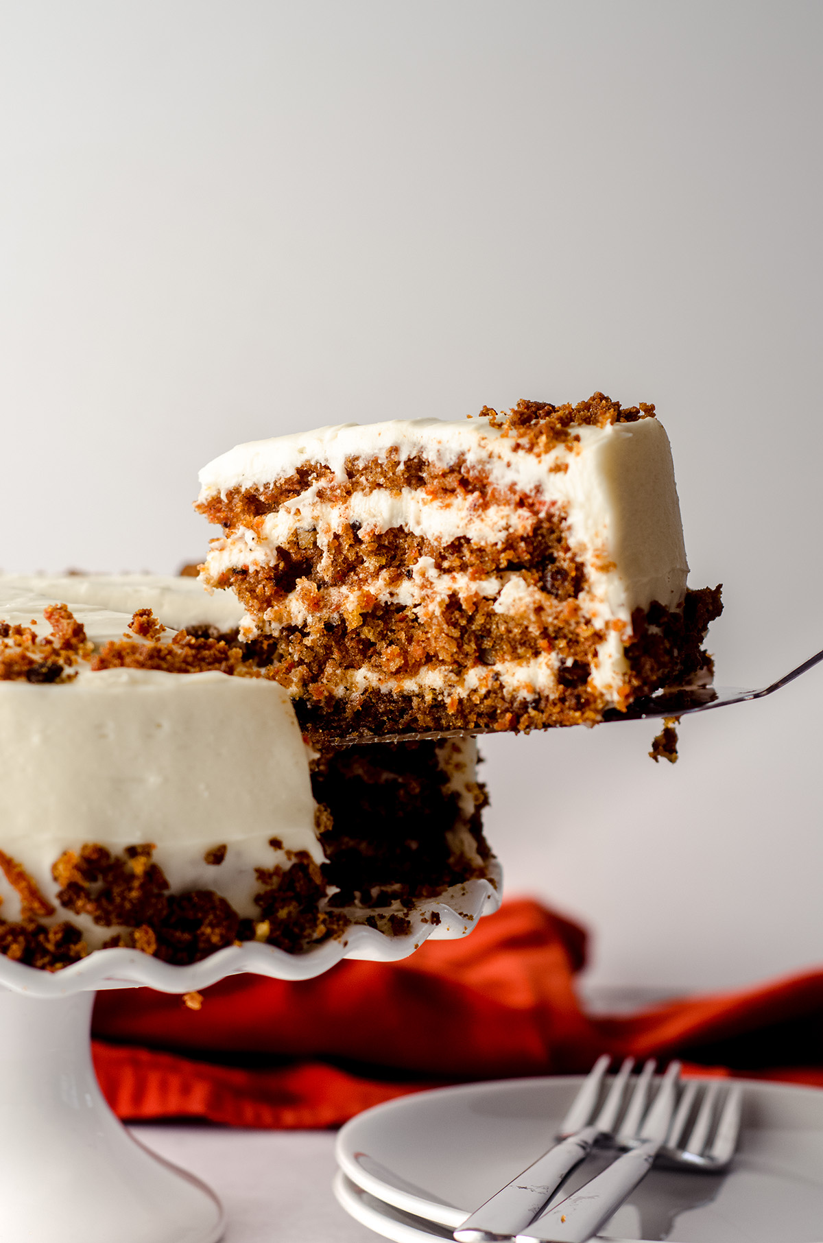a slice of carrot walnut cake being lifted out from the cake to serve