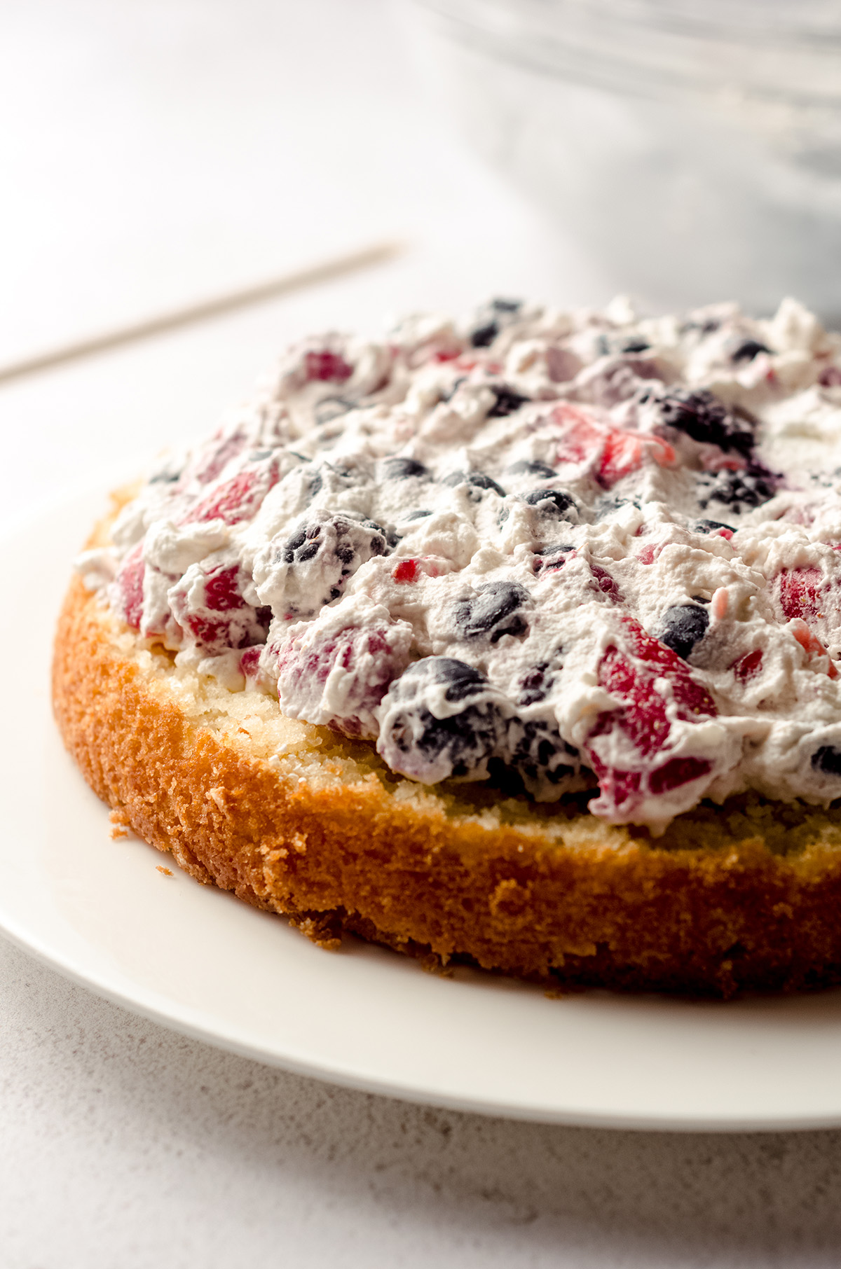 whipped cream and berry filling on a layer of berry cake
