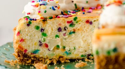 sliced funfetti cheesecake with whipped cream and sprinkles on top