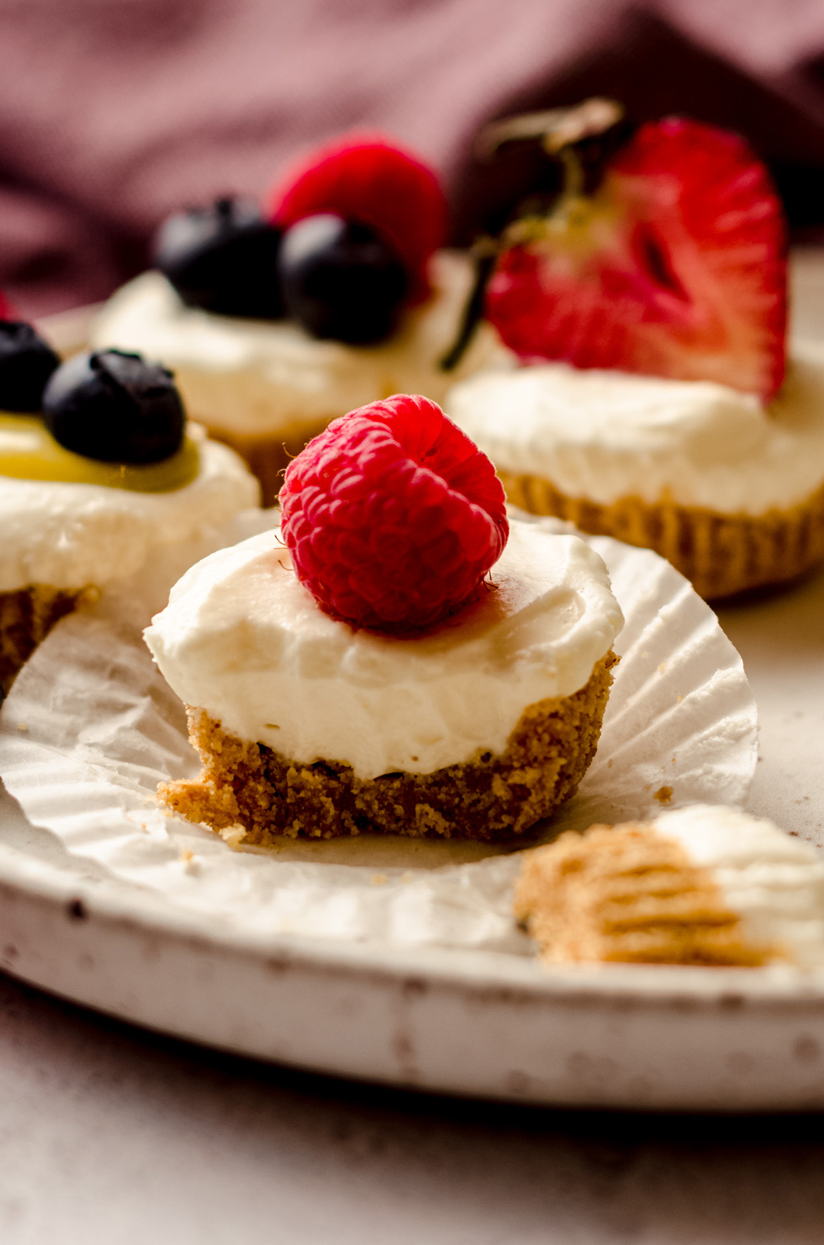 an unwrapped no bake cheesecake bite with a raspberry on top