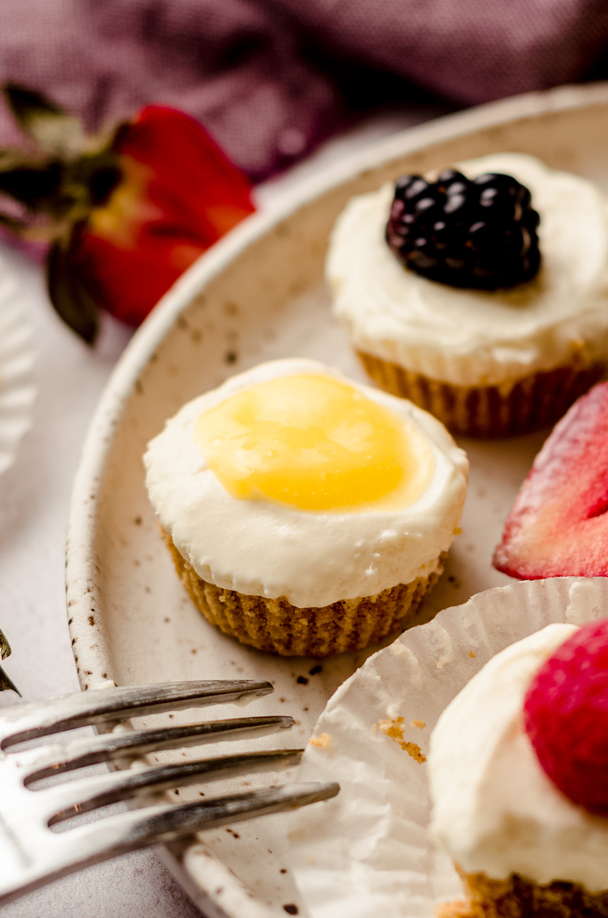 no bake cheesecake bites on a plate topped with lemon curd