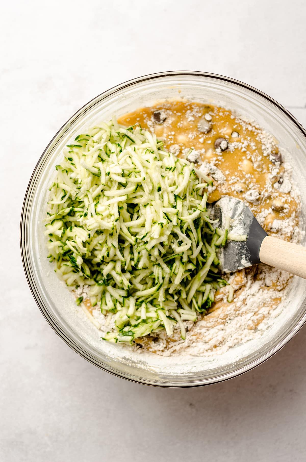 stirring shredded zucchini into chocolate chip zucchini bread batter
