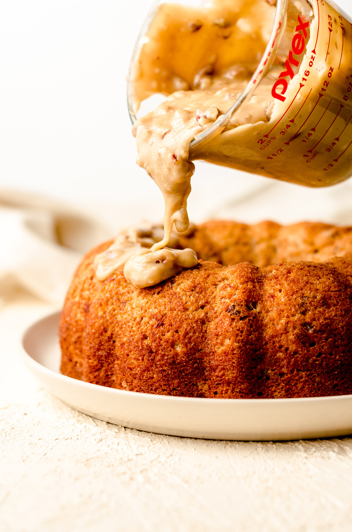 pouring pecan praline icing on a bananas foster cake