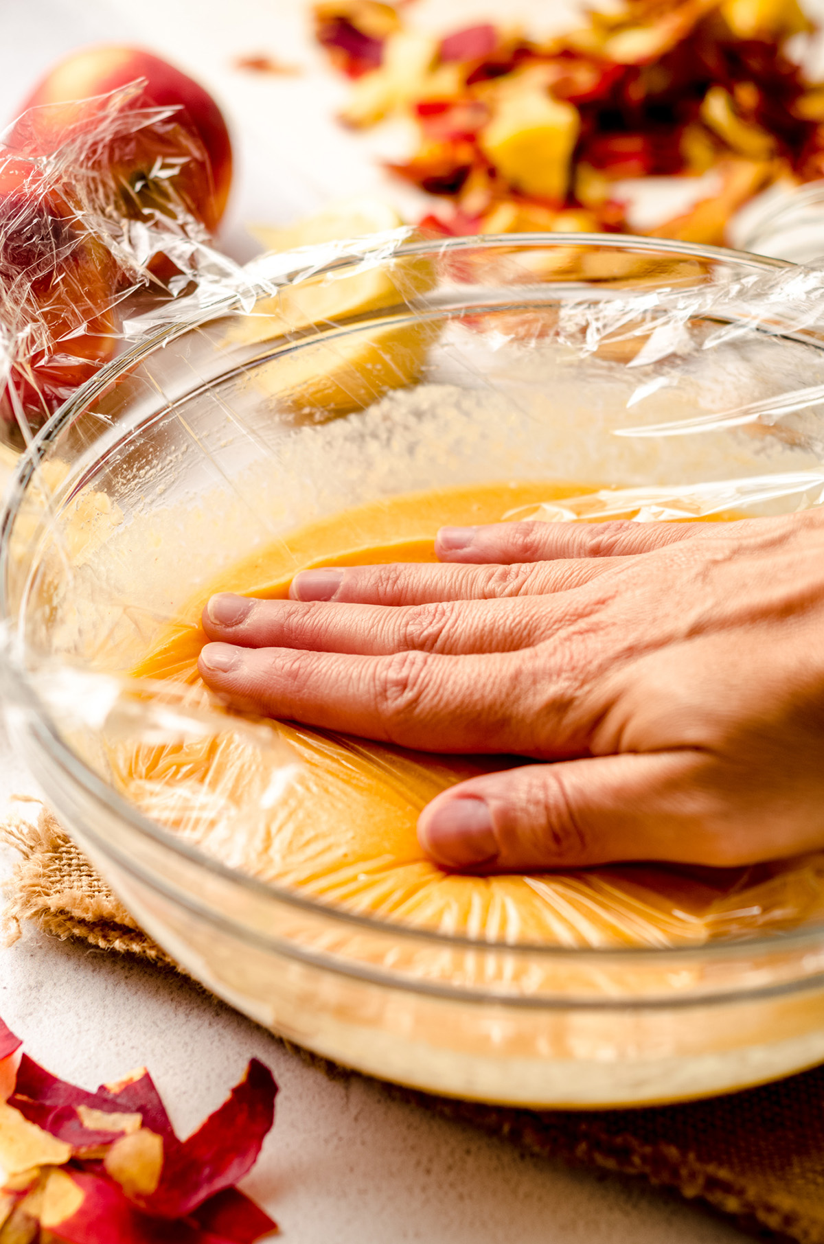 hand pressing plastic wrap onto peach curd