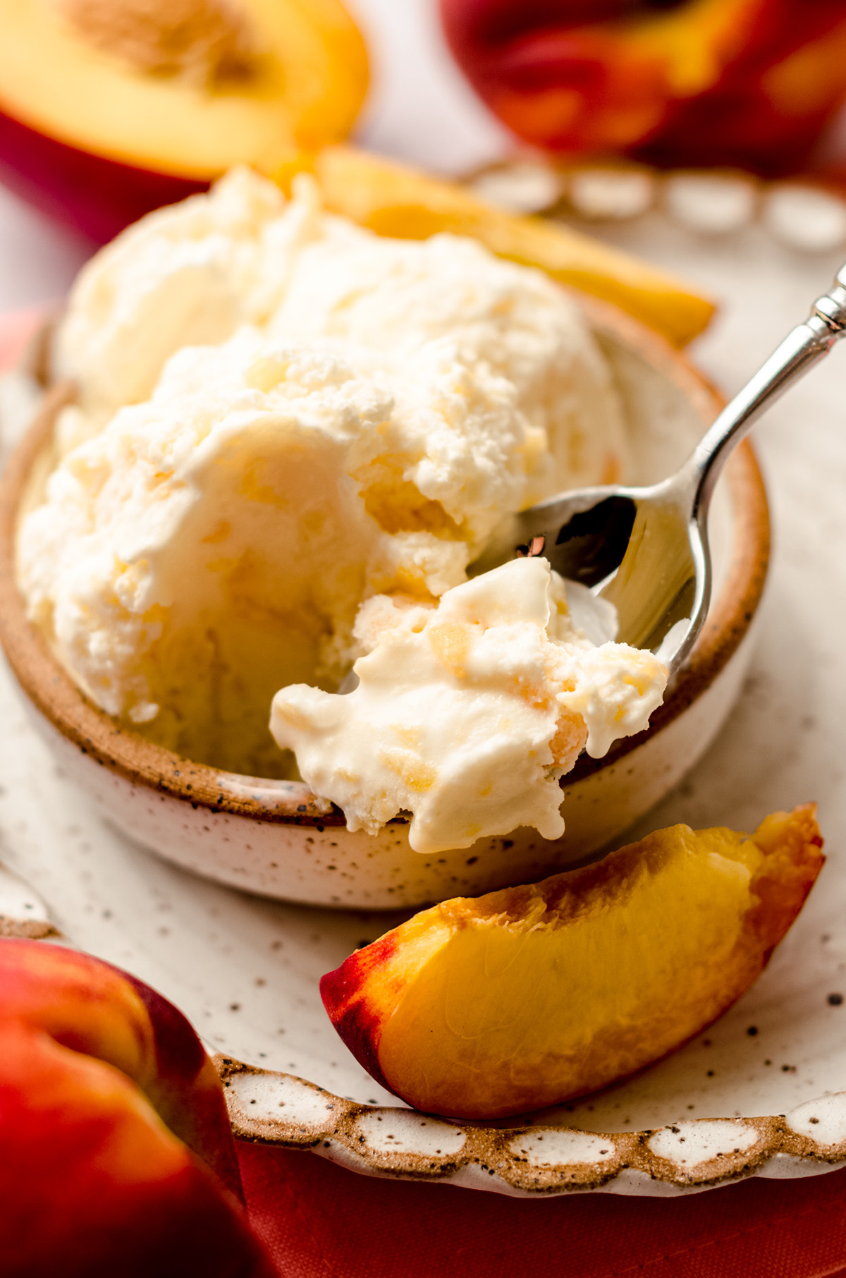a bowl of homemade peach ice cream with a scoop a spoon